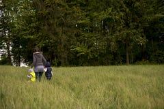Donna che cammina i suoi due bambini attraverso un campo Immagini Stock Libere da Diritti
