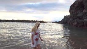 Donna che cammina lungo la spiaggia archivi video