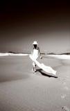 Donna che cammina lungo la spiaggia Immagini Stock