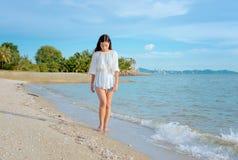 Donna che cammina lungo la spiaggia Immagini Stock Libere da Diritti