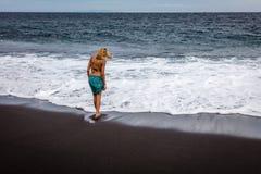 Donna che cammina lungo la spiaggia di sabbia nera in Padangbai, isola di Bali, Indonesia Immagine Stock