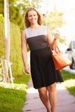 Donna che cammina lungo la via per lavorare fotografie stock libere da diritti