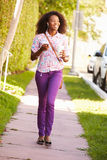 Donna che cammina lungo la via per lavorare ascoltare la musica fotografie stock