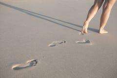 Donna che cammina lungo una spiaggia Fotografie Stock