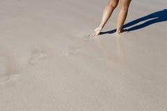 Donna che cammina lungo una spiaggia Immagini Stock