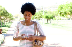 Donna che cammina nel parco che ascolta la musica sul telefono Fotografia Stock Libera da Diritti