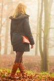 Donna che cammina nel parco nel giorno nebbioso Immagini Stock