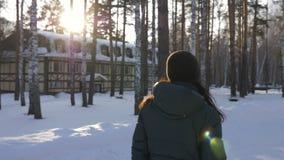 Donna che cammina nel villaggio del cottage di inverno mentre vista soleggiata della parte posteriore del tempo stock footage