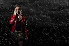 Donna che cammina nell'orizzontale della pioggia immagini stock