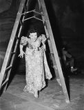 Donna che cammina sotto una scala a libretto con le sue dita attraversate (tutte le persone rappresentate non sono vivente più lu Immagini Stock