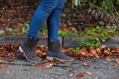 Donna che cammina su una via in pieno delle foglie durante l'autunno Fotografia Stock