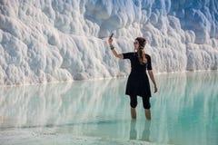 Donna che cammina sui terrazzi a Pamukkale Castello del cotone nel turco ed è sito naturale fotografia stock