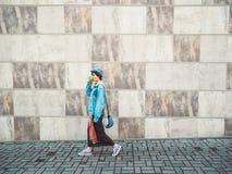 Donna che cammina sul corridoio all'aperto della parete dei marciapiedi grigi del fondo che tiene la tazza di caffè calda del caf Fotografia Stock