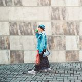 Donna che cammina sul corridoio all'aperto della parete dei marciapiedi grigi del fondo che tiene la tazza di caffè calda del caf Immagini Stock