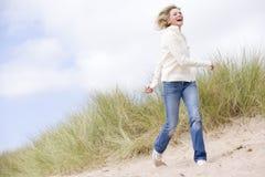 Donna che cammina sul sorridere della spiaggia Immagini Stock
