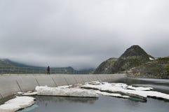 Donna che cammina sulla parete della diga dell'alta montagna in un giorno imbronciato freddo Immagini Stock