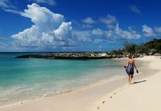Donna che cammina sulla spiaggia isolata Fotografia Stock