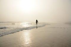 Donna che cammina sulla spiaggia nebbiosa Fotografie Stock