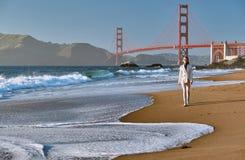 Donna che cammina sulla spiaggia vicino a golden gate bridge fotografie stock libere da diritti