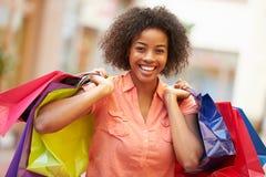 Donna che cammina tramite i sacchetti della spesa di trasporto del centro commerciale Immagine Stock