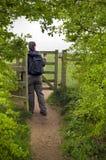 Donna che cammina tramite il cancello di legno in campagna Immagine Stock