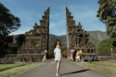 Donna che cammina tramite il portone tradizionale di Bali fotografia stock