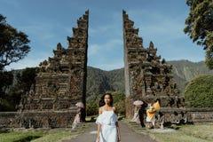 Donna che cammina tramite il portone tradizionale di Bali immagini stock libere da diritti