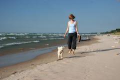 Donna che cammina un piccolo cane bianco sulla spiaggia Immagini Stock Libere da Diritti