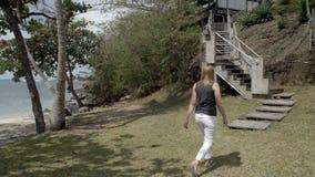 Donna che cammina verso le scale ad un bungalow video d archivio