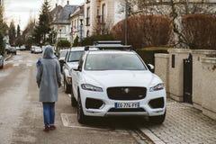 Donna che cammina vicino al F-passo di lusso SUV di Jaguar Fotografia Stock