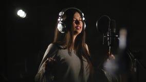 Donna che canta emozionalmente nello studio di registrazione stock footage