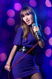 Donna che canta nel microfono Fotografia Stock