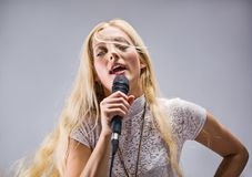 Donna che canta in un microfono Immagine Stock