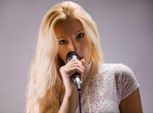 Donna che canta in un microfono Fotografie Stock