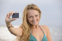 Donna che cattura foto con il cellulare sulla spiaggia Fotografia Stock Libera da Diritti