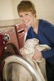 Donna che cattura lavanderia dall'essiccatore Fotografie Stock Libere da Diritti