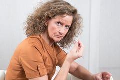 Donna che cattura le pillole fotografie stock