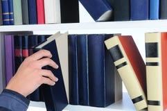 Donna che cattura libro dalla mensola Immagine Stock