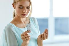 Donna che cattura medicina Bella ragazza con il pacchetto della pillola con le pillole Fotografia Stock Libera da Diritti