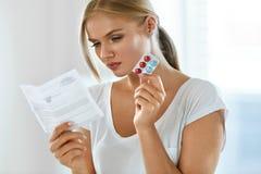 Donna che cattura medicina Femmina con le pillole che legge le istruzioni Immagini Stock