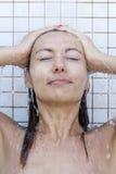 Donna che cattura un acquazzone Immagini Stock