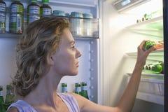 Donna che cerca alimento in frigorifero Fotografia Stock
