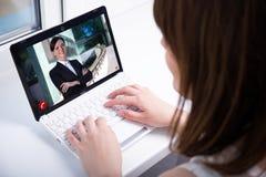 Donna che chiacchiera con il collega sopra una video chiamata Immagini Stock