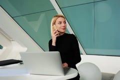 Donna che chiama con il telefono delle cellule durante il lavoro sul computer portatile nell'interno dell'ufficio Fotografia Stock Libera da Diritti