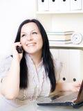 Donna che chiama dal telefono in ufficio Fotografia Stock