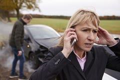 Donna che chiama per dichiarare incidente stradale sulla strada campestre Immagini Stock Libere da Diritti