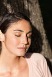 Donna che chiude i suoi occhi mentre sedendosi contro un albero come il sole s Immagini Stock Libere da Diritti