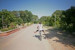 Donna che cicla fra le tempie di Bagan fotografia stock libera da diritti