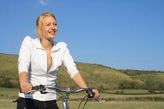 Donna che cicla nella campagna. Fotografia Stock