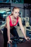 Donna che cicla in una palestra, durante in abiti sportivi Fotografia Stock